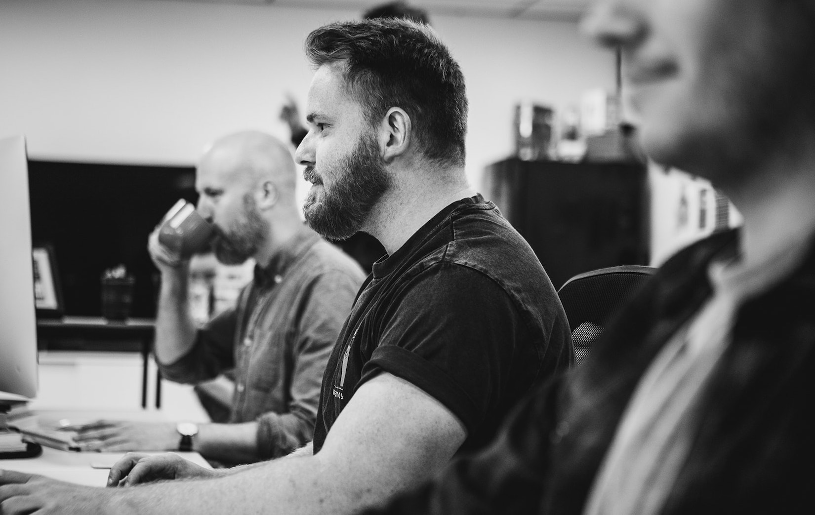 A black and white photograph of Framework's creative director working on a computer next to two other people.